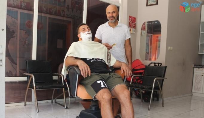 Berberden ilginç hizmet, hem tıraş ediyor hem serinletiyor