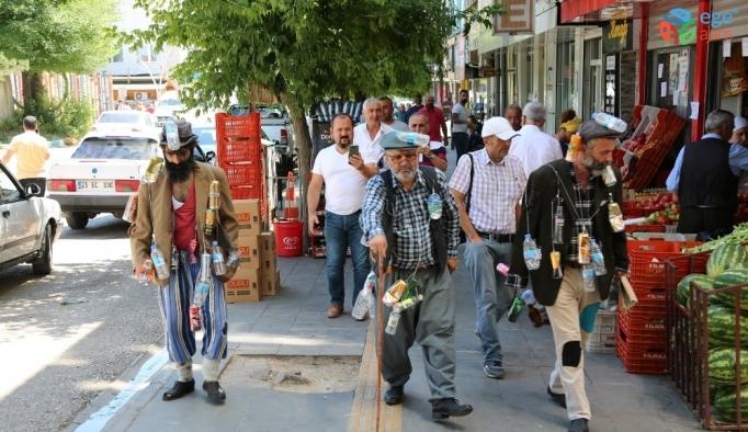 Çevre kirliliğine dikkat çekmek için vücutlarına astıkları çöplerle sokakları gezdiler